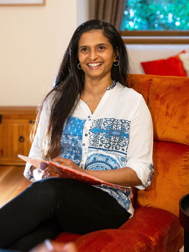 Usha Raman smiling sitting on a chair